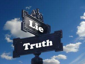 road sign saying lie one way and truth the other way